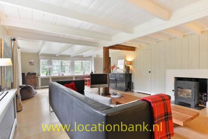 woonkamer met houtkachel en houten balken
